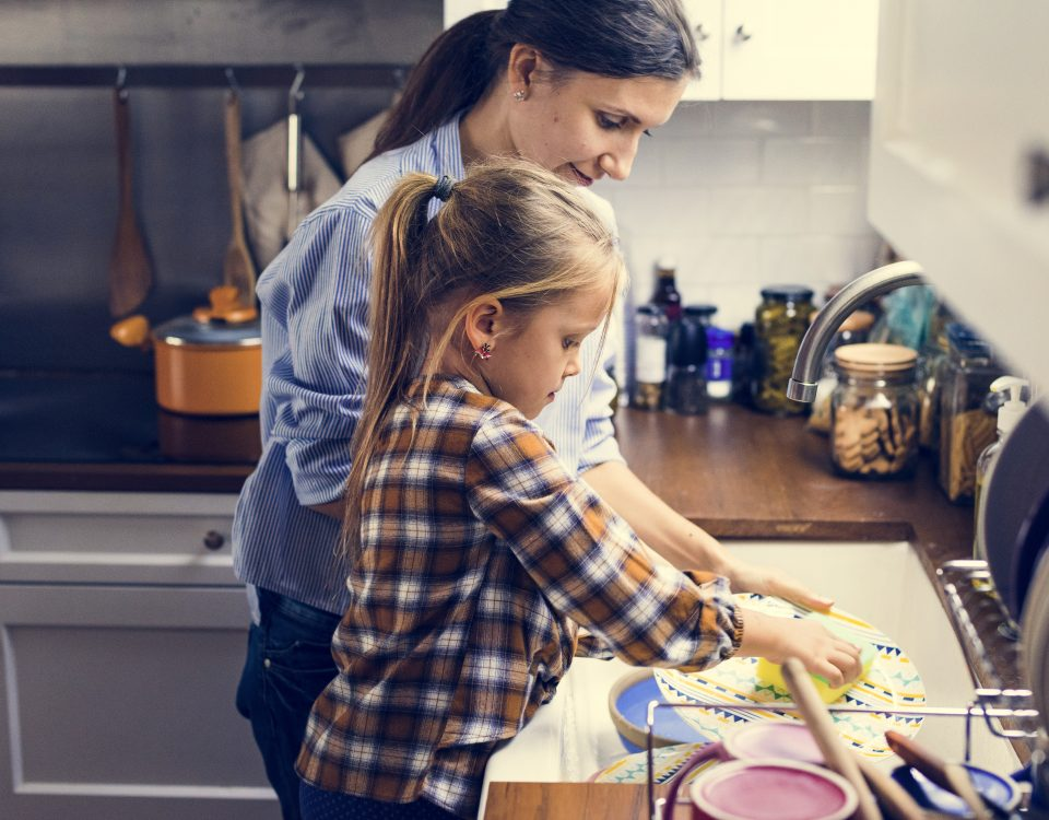 Daughter helping mom in cleaning dishes